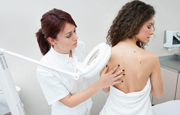 дерматолог изучает новообразование у девушки