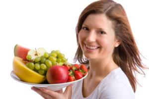 женщина держит фрукты в тарелке