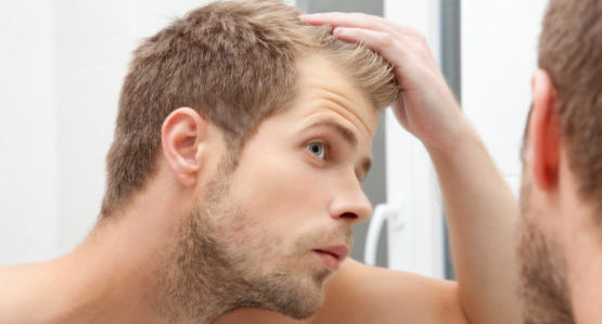 мужчина рассматривает голову в зеркале