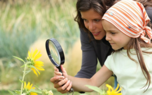 мама и дочь смотрят на цветок
