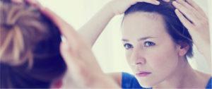 девушка рассматривает кожу головы в зеркале