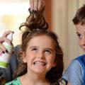 детям обрабатывают волосы спреем