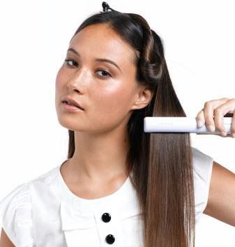 девушка обрабатывает волосы утюжком