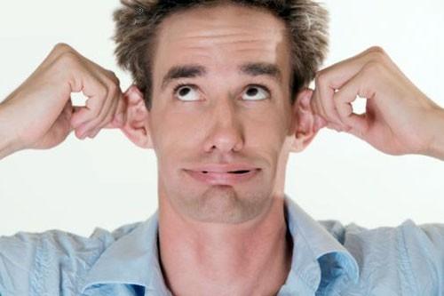 мужчина держится за уши