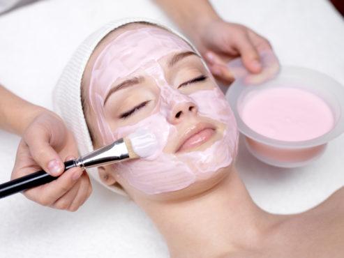девушке наносят розовую маску на лицо