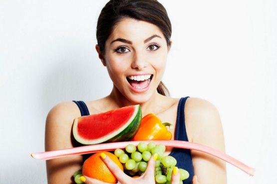 девушка держит свежие фрукты и овощи