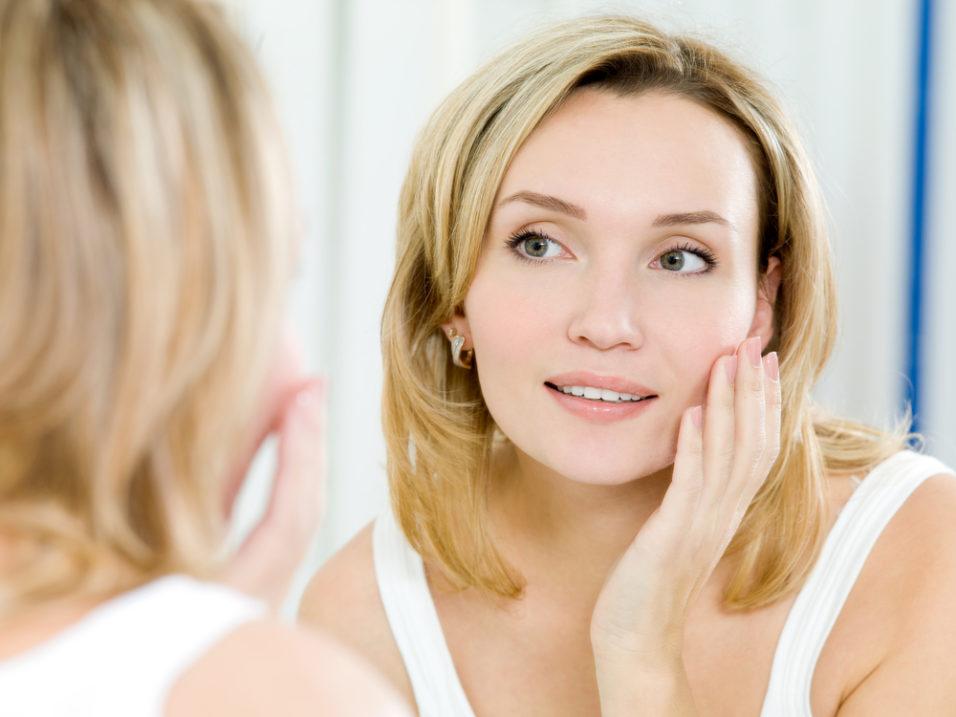женщина рассматривает лицо в зеркале