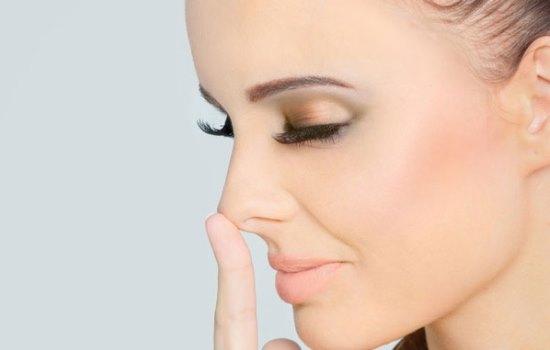 Девушка трогает свой нос