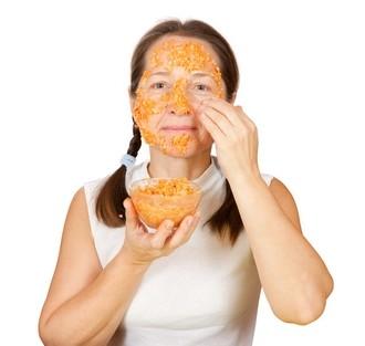 девушка наносит маску из творога и моркови