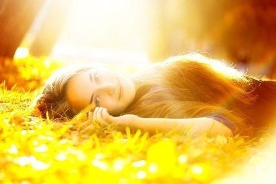 девушка лежит на лужайке в солнечных лучах