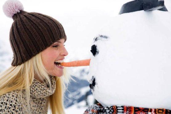 девушка кусает нос снеговика