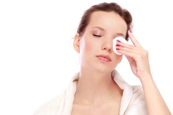 молодая женщина протирает глаза ватным диском