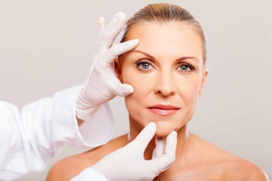женщине проводят осмотр кожи лица